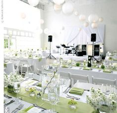 Both the ceremony and reception took place in the loft-style studio. For a fresh, clean feel, white became the primary wedding color, while shades of green popped up through the modern floral arrangements. Dozens of white paper lanterns also hung from the space's 20-foot ceiling.