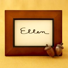 Turn a name card into a work of art by placing it in an inexpensive picture frame. Small ones for wallet-sized photos are the perfect size, and you can easily spruce them up by gluing on faux acorns or other festive items.
