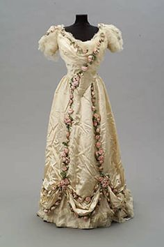 Circa 1907 Evening dress by Jean-Philippe Worth. Cream silk satin two-piece debutante dress, trimmed with cream silk net at sleeves, neckline, and skirt, with a cascading row of pink roses from right shoulder and down front bodice from left shoulder. Skirt hem caught up in swags, decorated with two rows of pink roses. Two rows of roses descending down front of skirt from waist to swagged hem.