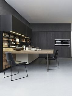 "Varenna_PHOENIX_kitchen with quarzo embossed lacquered base units, tall units in black elm, carbone embossed lacquered wall units. Worktop in micro-blasted nero sand quartzite thickness 1/4"". Back panel in walnut c. Carbone embossed lacquered equipped back Shaker."