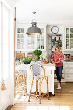 Chyka Keebaugh's Melbourne manor celebrates a collection of different decorating styles. In her entertainer's kitchen however, Hamptons style reigns supreme with cafe-style bar stools, glass-fronted cabinetry and marble benchtops. Photo: Martina Gemmola / *Australian House & Garden*