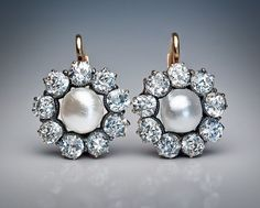 A Pair of Antique Natural Pearl and Diamond Cluster Earrings; circa 1910; 14K rose gold leverback earrings are centered with natural pearls; framed by sparkling bright white old European cut and old mine cut diamonds in silver and gold settings. Estimated total diamond weight - 3.50 carats; Diameter - 19 mm (9/16 in.)