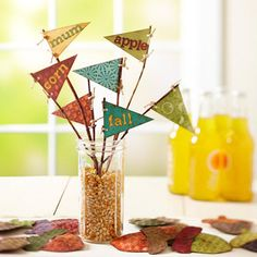 Start with muted colors and patterns of scrapbook paper; cut into pennant shapes and use adhesive scrapbook letters to spell out words. Punch two holes in each pennant and tie to a twig; tuck all into a glass jar filled with popcorn.