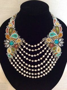 A delightful bead embroidery necklace featuring a collar of soft black leather encrusted with hundreds of glass seed beads in shades of turquoise, brick, pale mustard, olive, orange, black and white. Accented with ivory seed pearls, brass and silver beads, rhinestones and two round reconstituted turquoise beads. The beadwork is covered with a thin coat of resin to keep everything in place. One hundred and fourteen 7-8mm freshwater pearls in 8 graduated rows drape gracefully from the beaded…