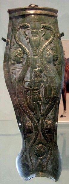 - Cnémida adornada con la figura de un gladiador tipo Murmillo o Mirmillón