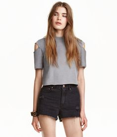 Gray. Short top in jersey. Short sleeves with open sections at shoulders and raw edges.