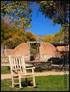 An empty rocking chair is framed by red rock cliffs and a gate at Ghost Ranch, north of Abiquiu.