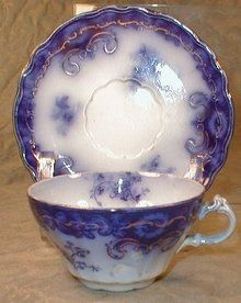 Henry Alcock & Company's Granada Flow Blue Cup & Saucer, circa 1880-1910, Pattern features an intricate border of vines & swags with floral sprigs in the open areas. The cobalt is accented with hand-painted gold trim.