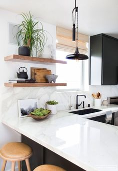 Cute black and white kitchen with some neutral accents and open warm wood shelving, marble backsplash