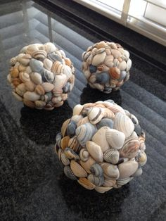 Schelpen plakken op een piepschuim bol. - Sea shells