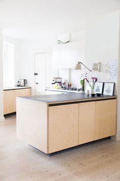Naja og Kristian har designet køkkenet med Ikea-elementer som indmad. Udvendigt har de brugt birketræsfiner, sort, indfarvet mdf og lagt en bordplade i sort linoleum på toppen af køkkenøen. Den skulpturelle glasskål fra Holmegaard på toppen af skabet er fundet på et loppemarked på Nørrebro