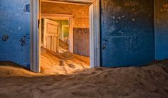 Kolmanskop, Namibia - The discovery of diamonds in the early 20th century sparked a mining rush, and German prospectors established a settlement here to mine the gems. The town was abandoned in 1954 after the supply began to dwindle and was finally exhausted. The desert winds swept in and blanketed the town in sand, making it one with the desert. Now the town can be explored on special tours, but nearly every building is covered in knee deep sand.