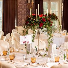 Rachel and Rob embraced the festive time of year when it came to decorating their wedding. Candelabras decorated the tables at the wedding reception, wrapped in red roses and trailing greenery by Corbins Florist. Alternating tables featured hurricane vases wrapped with roses.The tables were each named after one of Santa's reindeer, and featured a Christmassy card depicting them, which the couple had ordered and customised online. The table plan was displayed on a red poster with a snowy ...