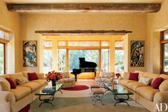 Paintings by Thomas Hart Benton flank a Steinway baby grand in the living room of the California home of philanthropists Joan and Sanford I. Weill, which is also outfitted with cocktail tables designed by the house's decorator, MAC II  | archdigest.com
