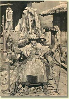 """Photos like this have been published in the past, featured in the book, """"Lost Tibet"""". The man depicted holds a bow in his left hand, clearly suggesting he is a part of the Monlam Festival where such men dress up in warrior costume. The round 'mirror' hanging from his neck is the type of thing that 'seers' or the oracles of the state wear. Clearly he is a special person posing for this photograph circa 1900."""