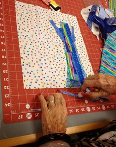Starting with a pile of scraps, she cuts and glues on pieces with a washable glue stick.- nifty quilts: Weekend with Freddy