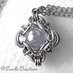A Saniki Creations exclusive original. Based on a variant of our own Aurora Chainmaille weave, Stainless Steel rings acts as prongs whichholds and secures the 10mm clear marble in the centre of the pendant.