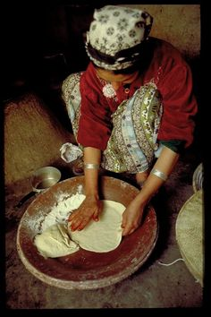 Berber woman making flatbread. Actually experienced this after a trek through the Sahara. An old Berber woman made us flatbread in a stone fire and served it with olive oil and tomatoes. It was a wonderful experience to see how different cultures make food and live.