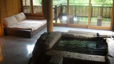 """日本ではじめて露天風呂付き客室を誕生させたのがこのお宿。日本全国のお宿が客室付き露天風呂を取り入れるようになった現在、雅叙苑はさらなる進化を遂げました。それがこの""""お風呂リビング""""。露天風呂に屋根と壁、窓をつけ、さらに床暖房も設置。裸で寝転べるデイベッドやソファを配し、湯冷ましのテラスも完備したまさに「お風呂が中心にあるリビングルーム」。本を読んだり音楽を聴いたりしながら一日中お風呂で過ごせる、夢のようなお部屋です。"""