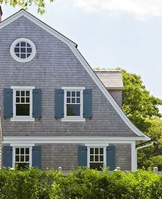 Gambrel rooflines, shutters & shingles. Gray with white trim.  The round window.