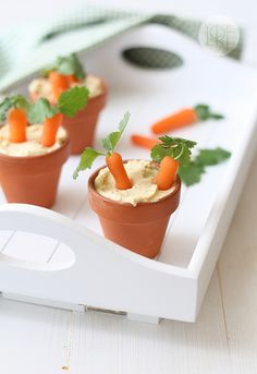 "Hummus w/ Roasted Garlic (serve hummus in small terracota pots with baby carrots. Just before serving, poke a hole in the top of each baby carrot with a toothpick and insert a sprig of cilantro or parsley into each hole. ""Plant"" a couple of baby carrots in each pot, and enjoy!)"