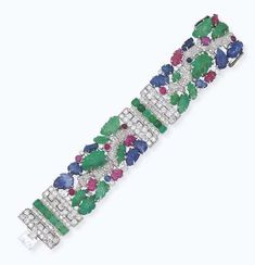 AN ART DECO 'TUTTI FRUTTI' GEM-SET BRACELET, BY CARTIER  The carved emerald, sapphire and ruby leaves with pavé-set diamond branches and cabochon collet detail to the diamond and cabochon emerald geometric link spacers, mounted in platinum, circa 1930