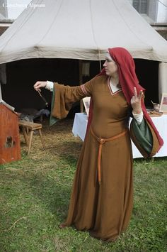 Woman spinning, wearing a bliaut. Comthurey Alpinum, 12th century Medieval Reenactment 1180 ad.