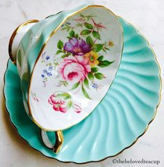 Antique floral tea cup on bright blue saucer.