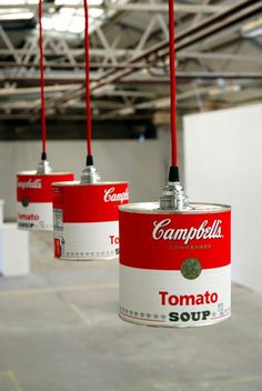 """These are """"campbells tomato soup"""" cans hung from the ceiling with bulbs inside them. They are inspired by Andy Warhols famous soup can piece, which could inspire me to base my lamp design off of a famous artwork. These lamps are also just recycled cans, which is an idea I could use in my design because the design should be within a budget and also be environmentally friendly."""
