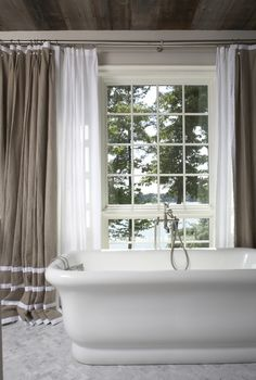 plank ceiling, linen drapery, herringbone marble floor, window, tub, faucet  (designed by Tracery Interiors)