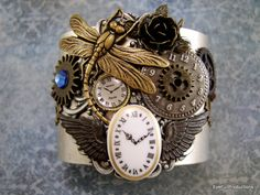 """This cuff is loaded. Brass dragonfly, gears, crystals, clock faces, wings, silver ox filigree adorn the antique silver cuff. The cuff is 2"""" wide and somewhat adjustable. Your bracelet will arrive in a box for gift giving or safe storage. Handcrafted USA 2013  #cuff #antiquesilver #cuff #bracelet #steampunk #handmade #thecraftstar #shop"""