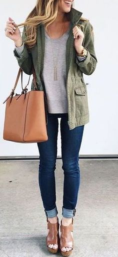 Military green jacket, grey sweater, skinny jeans, camel ankle boots & tote, long gold pendant necklace