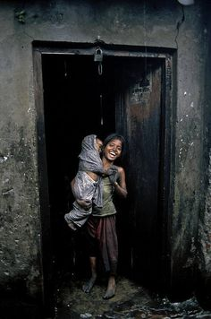 """6-18 taka is 7-22 cents a day, in USD    """"During a short break from her work, Hajira laughs standing on the door of workshop. She is carrying her three years old sister Mumtaz in her arms. She works with her mother, but also help look after her two younger siblings. Hajira gets paid between Taka 6-18 per day.""""    from Shehzad Noorani's Flickr set, Children of Black Dust"""