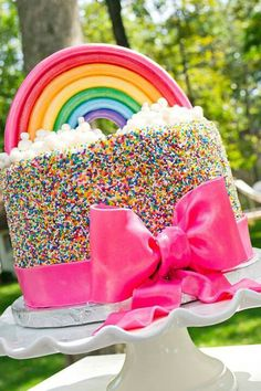 Lovely Rainbow Cake - I like the colors she used instead of Primary colors. And both the bow & rainbow is pearly.