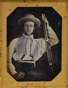 C. 1847 1/4 Plate Daguerreotype of a Frontiersman. Wears pinstripe shirt with long cravat. Wide brimmed beaver hat. Narrow waist belt with roller buckle with silver mounted Sheffield Bowie knife and bar hammer pepperbox tucked in the front. Holds .69 caliber smoothbore musket at his side.