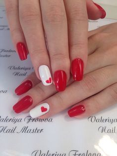 Caramel red manicure with small hearts on a white background reveals the passion of nature and gives a bright mood. ...