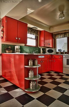 Lovely red kitchen with black-and-white tiled floor...I don't know. I'm kind of liking the red cabinets.