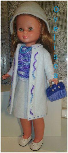 Muñeca Nancy conjunto nieve y cielo. Abrigo falda y gorro blancos. Jersey punto azul y morado. Bolso punto azul y morado.