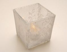 buy a cheap glass candle holder and lace. use a product called Mod Podge to brush over the lace on the holder.