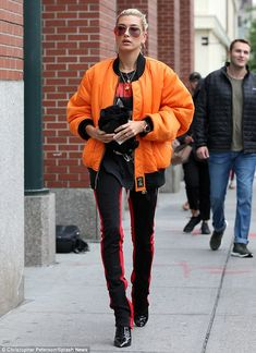 Model behavior:Hailey looked as if she stepped off the runway in a bold orange puffy jack...
