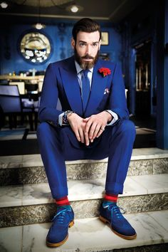 Shop this look on Lookastic:  https://lookastic.com/men/looks/suit-dress-shirt-brogues-tie-pocket-square-lapel-pin-watch-socks/11509  — Red Floral Lapel Pin  — Blue Knit Tie  — White and Navy Print Pocket Square  — Blue Horizontal Striped Watch  — White and Navy Vertical Striped Dress Shirt  — Blue Suit  — Blue Suede Brogues  — Red Socks