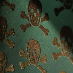 Skulls Bronze on Oil Slick wallpaper by Firefly House Splash out with this on-trend wallpaper featuring skulls in a reflective bronze velvet on a iridescent base.