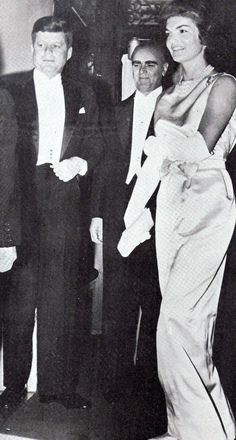 A simple white satin sheath gown was worn by Jacqueline Kennedy at a dinner party in the Greek Embassy hosted by Greece's Prime Minister Constantine Caramanlis, at center. (Scan by jackieandaudrey from the magazine A Salute To Jacqueline Kennedy).
