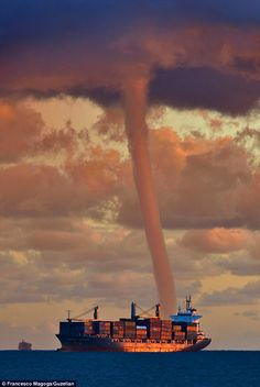Close call: This twister passed so close to the ship pictured that it appeared to be towering over it