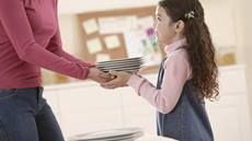 Close-up of a mother handing plates to her daughter who is helping set the table