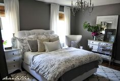 A frumpy guest bedroom gets a glamorous makeover with rich gray paint, a chandelier, mirrored dresser, tufted headboard and crisp linens. Via dearlillieblog.blogspot.com