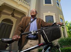 Clarence Walker standing holding his bike in front of a Victorian home... One of the best professors I learned from in college!