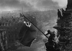 9. Soviet Flag raised above the Reichstag [Berlin, 1945]        Soviet Union soldiers Raqymzhan Qoshqarbaev, and Georgij Bulatov raising the flag on the roof of Reichstag building in Berlin, Germany in May, 1945. The photograph was taken by Yevgeny Khaldei.