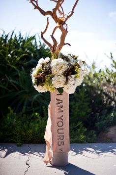 Driftwood and earth toned hydrangeas in carved wooden vases.