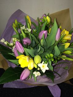 Spring bouquet of lilac and yellow tulips screens sols and daffodils wrapped in brown craft paper   #pennyjohnsonflowers